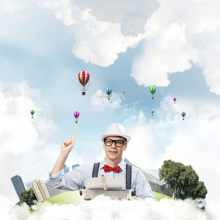 Young man writer in hat and eyeglasses using typing machine and pointing upside while sitting at the table with floating city and cloudy skyscape with flying aerostats on background.