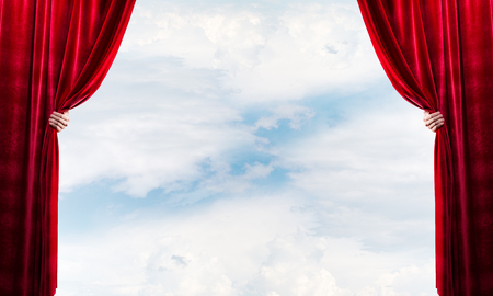 Human hand opens red velvet curtain on blue sky background Stock Photo - 116258278