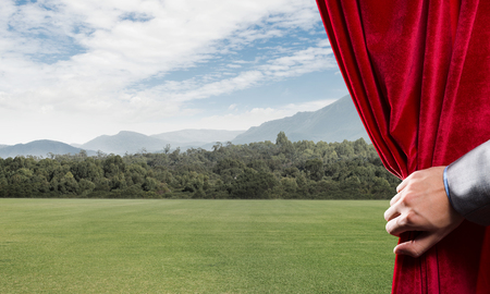 Human hand opens red velvet curtain to landscape with road Stock Photo - 116309842