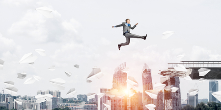 Businessman jumping over gap with flying paper planes in concrete bridge as symbol of overcoming challenges. Cityscape with sunlight on background. 3D rendering. Banco de Imagens - 116311302