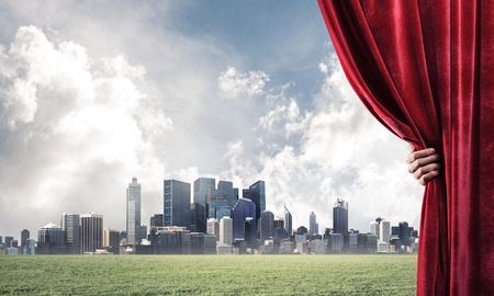 Human hand opens red velvet curtain to cityscape and green meadow Stock Photo - 116366654