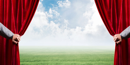 Human hand opens red velvet curtain to landscape with green grass Stock Photo - 116367640