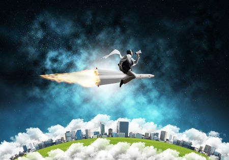 Conceptual image of young businessman in suit flying on rocket with planet Earth and open space on background. Stock Photo