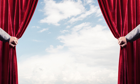 Human hand opens red velvet curtain on blue sky background Stock Photo - 116381306