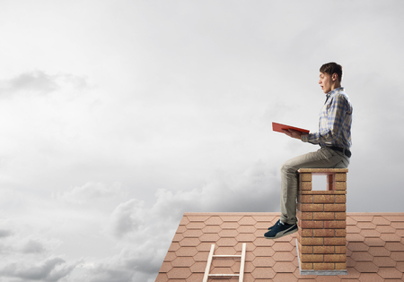 Young man in casual sitting on house chimney with red book in hands Foto de archivo