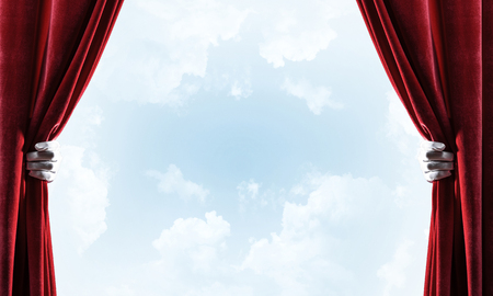 Human hand in glove opens red velvet curtain on blue sky background Stock Photo - 116386796