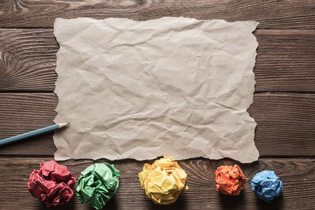 Crumpled brown paper sheet and pencil on wooden table Stock Photo - 116305756