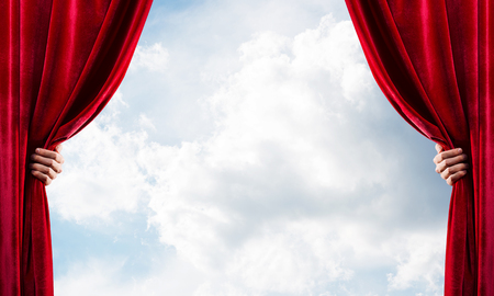 Human hand opens red velvet curtain on blue sky background Stock Photo - 116389933