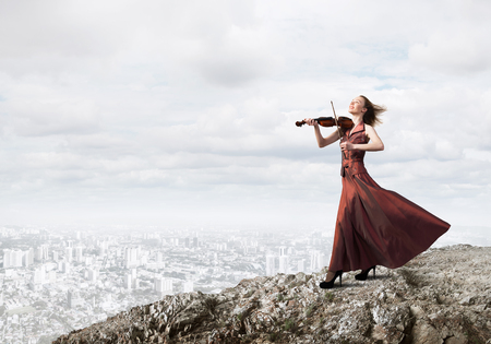Young attractive girl playing violin over cityscape background