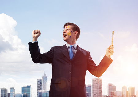 Horizontal shot of cheerful and young businessman in black suit gesturing and smiling while standing against cityscape view and cloudy sky on background