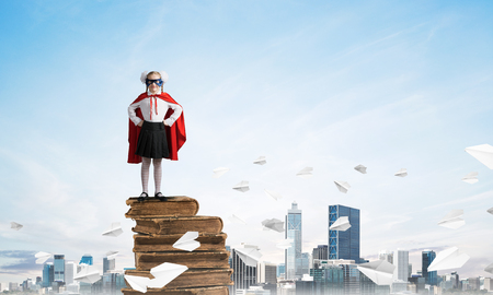 Young girl in superhero costume standing on pile of old books. Mixed media