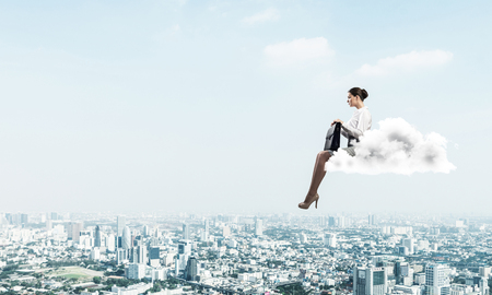 Young elegant woman with suitcase in hands siting on cloud Stock Photo