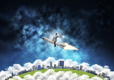 Conceptual image of young businessman in suit flying on rocket with planet Earth and open space on background. 免版税图像
