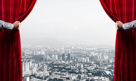 Ręce biznesmena otwierające czerwoną aksamitną kurtynę i pejzaż miejski w tle
