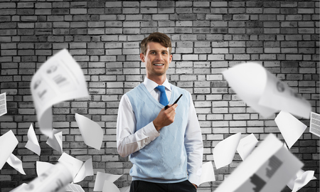 Horizontal shot of confident and young businessman in smart-casual wear smoking pipe while standing among flying papers and against gray dark wall on background.