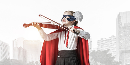 Little confident child in mask and cape plays violin against sunset background