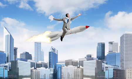 Conceptual image of young and happy businessman in suit flying on rocket with modern cityscape with skyscrapers and blue sky on background. 免版税图像