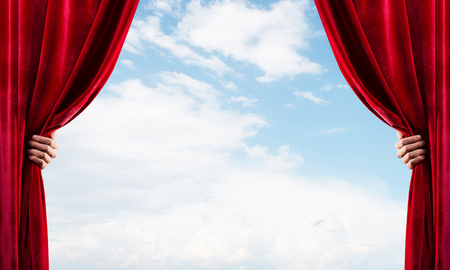 Human hand opens red velvet curtain on blue sky background Stock Photo - 116569569