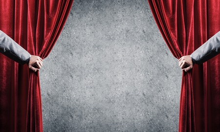 Close up of businessman hand open red velvet curtain. Place your text
