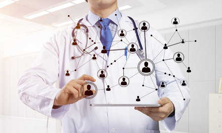 Cropped image of young doctor in white medical suit holding tablet with social network connection while standing inside bright office building 스톡 콘텐츠