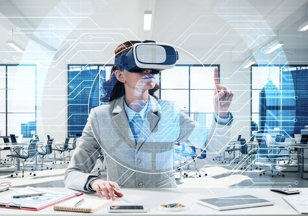 Conceptual image of confident and successful business woman in suit sitting inside office building with security interface and using virtual reality headset