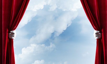 Human hand in glove opens red velvet curtain on blue sky background Stock Photo - 116569456