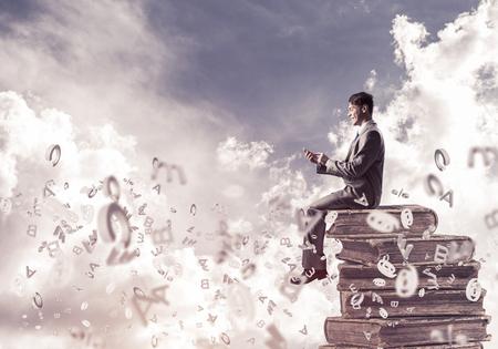 Jeune homme d'affaires assis sur une pile de livres avec un téléphone portable dans les mains