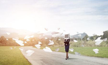 Business woman in suit with monitor instead of head keeping arms crossed while standing on the road among flying paper planes with beautiful landscape on background.