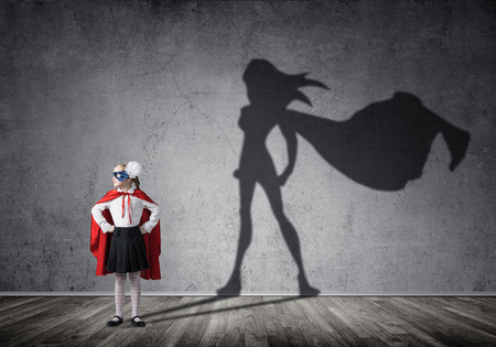 Little confident child in mask and cape plays cool superhero. Mixed media Stock Photo