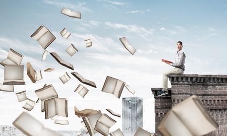 Young shocked man sitting on building edge with red book in hands