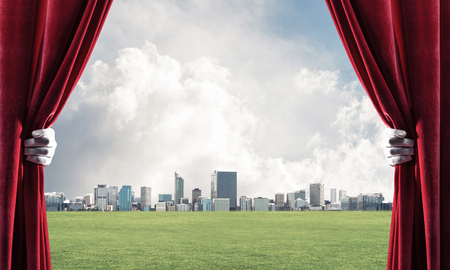 Human hand in glove opens red velvet curtain to cityscape and green meadow