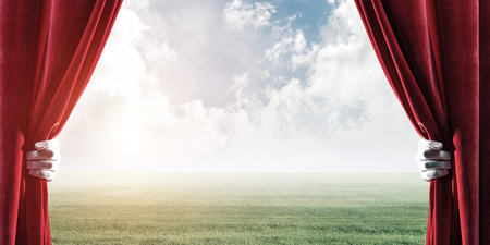 Human hand opens red velvet curtain to landscape with green grass Stock Photo - 116843140
