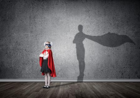 Kleines selbstbewusstes Kind in Maske und Umhang spielt coolen Superhelden. Gemischte Medien