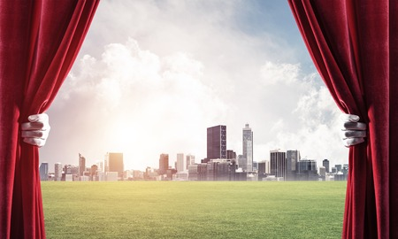 Human hand in glove opens red velvet curtain to cityscape and green meadow Stock Photo - 116844752