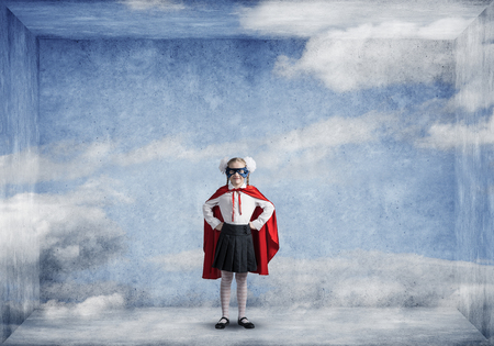 Little confident child in mask and cape in empty room plays cool superhero. Mixed media