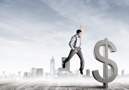 Young furious businessman going to crash with fist stone dollar symbol Foto de archivo