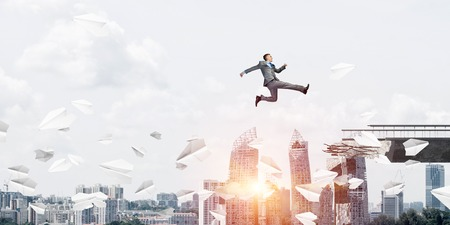 Businessman jumping over gap with flying paper planes in concrete bridge as symbol of overcoming challenges. Cityscape with sunlight on background. 3D rendering. Banco de Imagens - 116892765