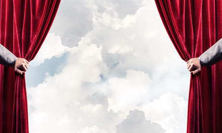 Human hand opens red velvet curtain on blue sky background Stock Photo - 116892802