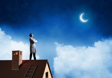 Horizontal shot of young doctor in white medical uniform standing at top of brick roof and with night skyscape view on background.