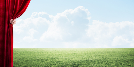 Human hand opens red velvet curtain to landscape with green grass Stock Photo - 116893070