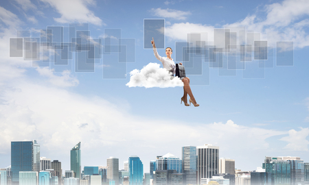 Businesswoman sit on cloud over city and pointing at icon in air Banco de Imagens