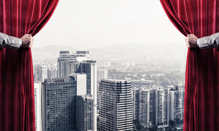 Hands of businessman opening red velvet curtain and cityscape at background Stock Photo