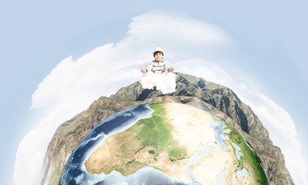Young little boy keeping eyes closed and looking concentrated while meditating on clouds in the air with panoramic view of Earth globe on background.