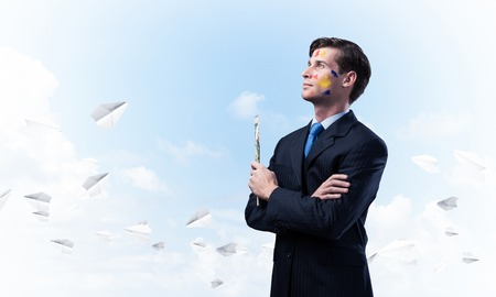 Portrait of young thoughtful man holding paintbrush in his hand and looking away while standing against blue cloudy skyscape with flying paper planes on background.