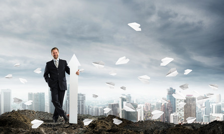 Horizontal shot of confident business man holding white arrow while standing among flying paper planes in ruins with cityscape view on background. Foto de archivo