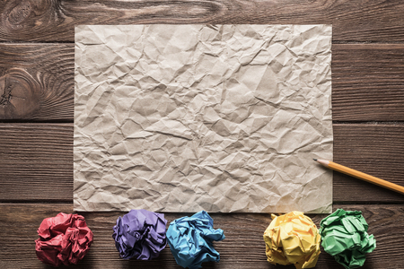 Crumpled brown paper sheet and pencil on wooden table Stock Photo - 117082606