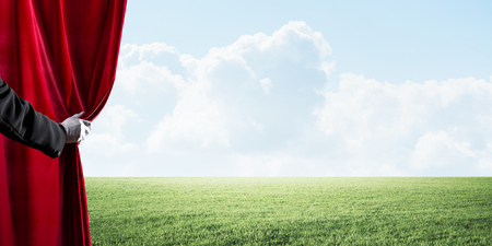 Human hand in glove opens red velvet curtain to landscape with green grass Stock Photo