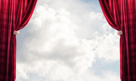 Human hand opens red velvet curtain on blue sky background Stock Photo - 117167807