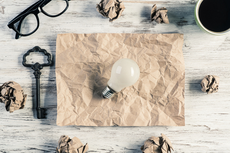 Top view of modern creative workplace with lightbulb on creased piece of sheet, crumpled paper balls, key and cup of coffee placed on wooden table. Concept of finding of outstanding idea.