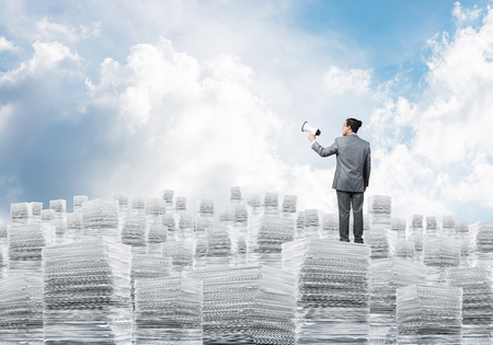 Businessman in suit standing on pile of documents with speaker in hand with cloudly skyscape on background. Mixed media. Stock Photo